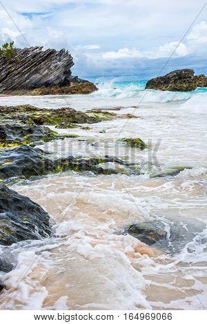 Sea water crashes against the lava rocks in scenic Horseshoe Bay Bermuda.