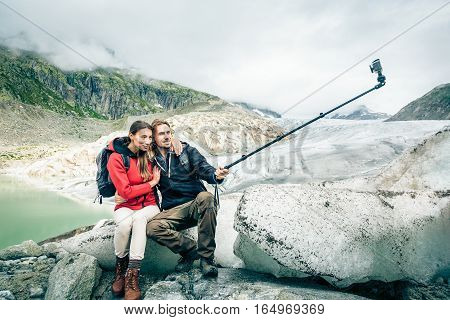 Young Couple Hiking in the Swiss Alps, Taking a Selfie. This is a generic, low-cost camera and not the 'famous original' brand.