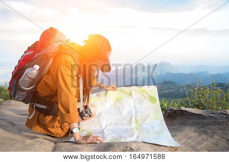 Women hiker with backpack checks map to find directions in wilderness area