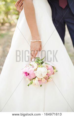 Bride. Bridal bouquet. Bride holding a bouquet. Wedding photo concept. Summer wedding.Sensual Wedding Photo. White peonies