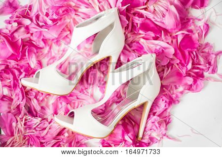Bride's shoes. White bride's shoes on the petals of peonies. Wedding photo concept. Summer wedding.