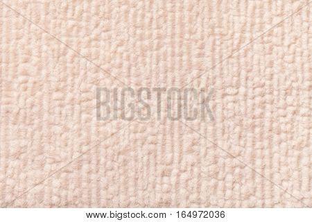 Light beige fluffy background of soft fleecy cloth. Texture of textile closeup