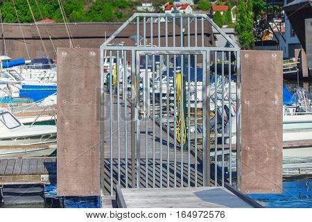 Ships boats and yachts harbor in Sandefjord Norway. Metallic gates.