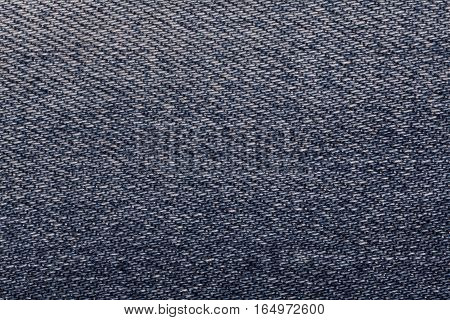 Navy blue shabby denim textile background closeup. Textured fabric macro