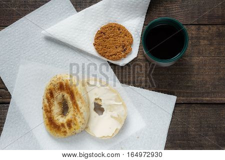 Bagel with cheese cookie and coffee on dark wooden background brekfast outside