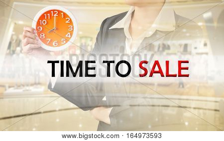 Time to sale and business woman holding clock on blurred shopping mall. Business concept.