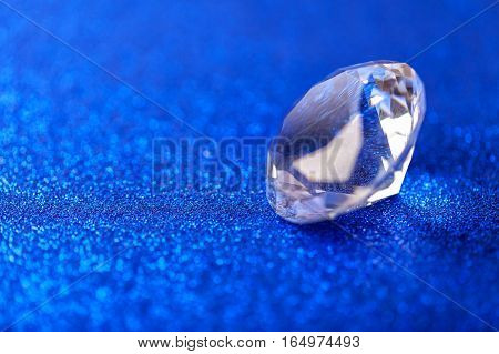 Grand royal pure diamond on blue sparkling sequins background macro . Big brilliant closeup.