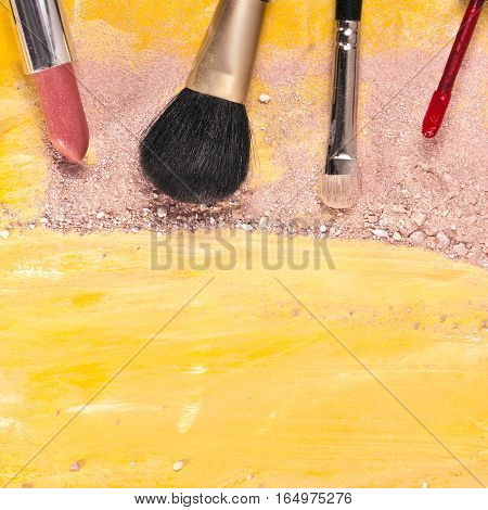 Makeup brushes and lipstick on a vibrant golden yellow background, with traces of powder and blush on it. A square template for a makeup artist's business card or flyer design, with copyspace