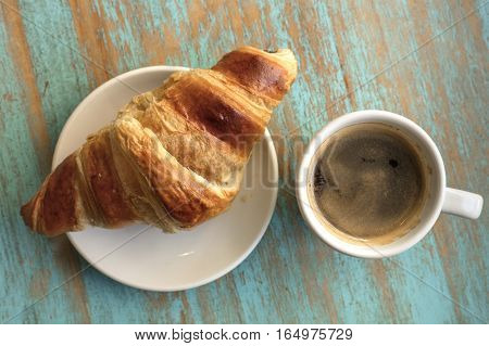 An overhead photo of cup of dark coffee with a croissant, on a teal blue wooden board texture with copyspace