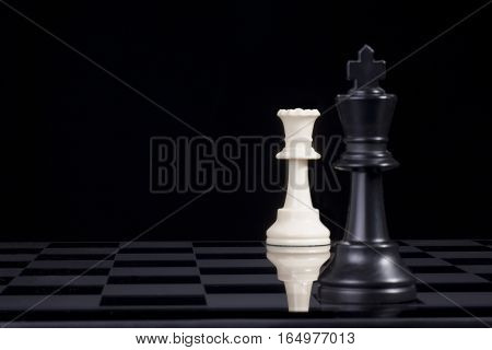 A black chess king in checkmate by white queen.