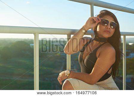 Young glamur brunette woman on metal stairs in sunset time