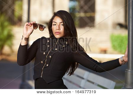 young hispanic woman hold sunglasses on day urban background
