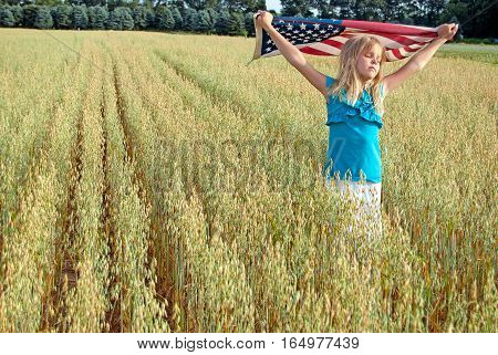young girl in Michigan wheat field with American flag