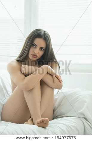 Beautiful half-naked girl posing on the bed