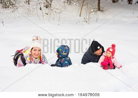 Happy family of four members lying down in snow in a row