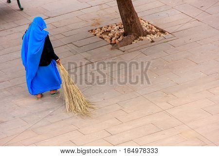 Woman sweeping Jaleb Chowk - main courtyard of Amber Fort Rajasthan India. Amber Fort is the main tourist attraction in the Jaipur area.