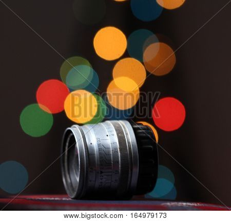 Old retro camera lens on bokeh background