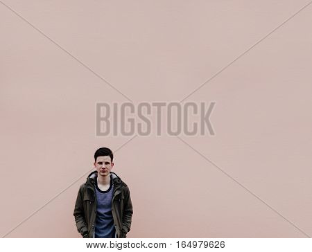 Young man in jacket on the background of the big pink wall, photo with place for text or other