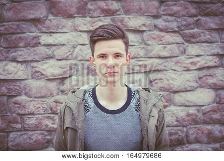 Young beautiful seriosly man on the city brick wall background