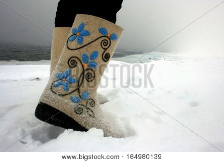 Russian traditional winter boots -felt boots (valenky) embroidered with blue flowers in the snow at the Angara River. Siberia. Russia.