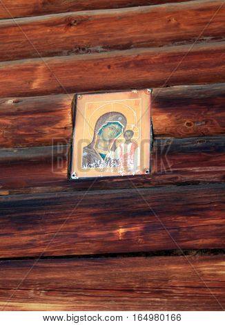 Icon of Mary Mother of God and Christ child in Russian traditional wooden house from logs. Traditional Russian architecture in Siberia. Winter house. Taltsy. Irkutsk. Russia.