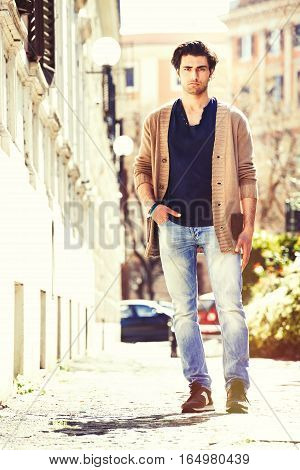 Gorgeous men outdoors, urban scene in the city. He stands walking on a street near a historical palace.