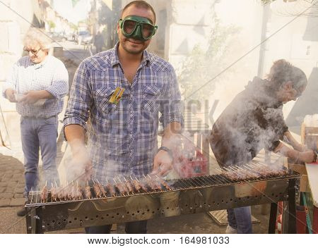 MANZIANA ITALY - OCTOBER 15 2016: Street vendor cooking lamb skewers on barbecue during the Chestnuts Festival an event where good food art music and traditions come together.