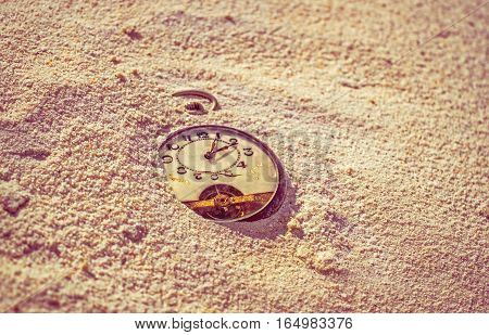 Sands of time. Antique rotten pocket watch buried in the sand, on the beach.