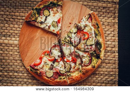 Delicious Pizza With Salami, Cheese, Peppers And Meat, Cut Into Slices.