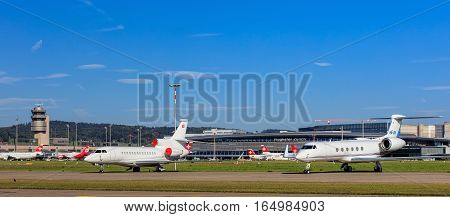 Kloten, Switzerland - 29 September, 2016: view in the Zurich Airport with Falcon 7X and Gulfstream V jets in the foreground, airport tower and building in the background. The Zurich Airport is the largest airport in Switzerland.