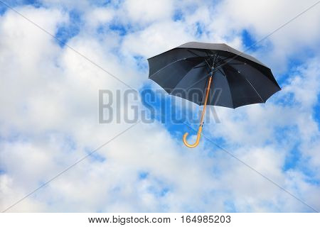 Black umbrella flies in sky against of pure white clouds.Mary Poppins Umbrella.Wind of change concept.