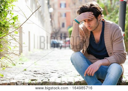 Anxiety. Thoughtful young man anxious, outdoors. A young and handsome boy is sitting on the street with one hand on the forehead. Anxiety, thoughts and concerns, problems concept.