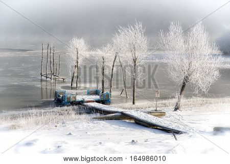 Lake covered by ice. Quiet winter days near water reservoir. Liptovska Mara. Frozen trees and water.