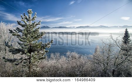 Lake Liptovska Mara Slovakia covered in ice.on a quiet winter days. Backround of ow Tatras mountains Slovakia