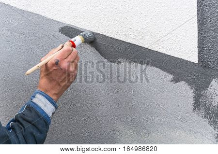 Close-up arm of a house painter with paint roller in hand painting a house wall with gray paint.
