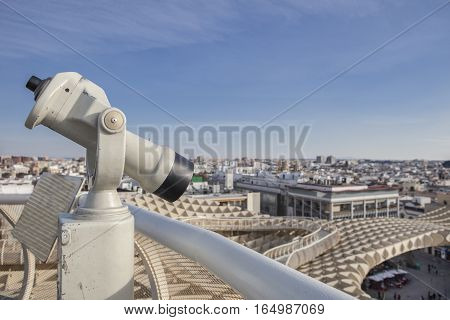 Turistic telescope pointing to old town landmarks over Metropol Parasol roof one of the best view of the city of Seville Spain