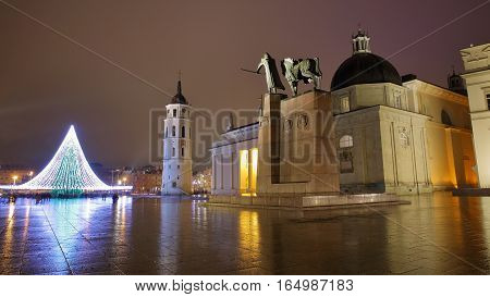 VILNIUS, LITHUANIA - JANUARY 1, 2017: Cathedral Square by night with from left to right: The illuminated Christmas tree, the Belfry (Cathedral Clock Tower) and the Cathedral - Gediminas Monument in the foreground