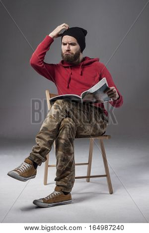Man with a beard. Bearded reads the news. Space for text. The guy sitting on a chair and reading hot news