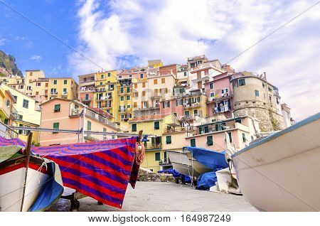 Manarola town Riomaggiore La Spezia province Liguria northern Italy. View of the colourful houses on surrounding hills boats balconies and windows. Part of the Cinque Terre National Park and a UNESCO World Heritage Site.