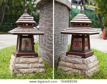 In and out signs on Asian wooden lanterns in a shape of pagoda. Directional lamps at entrance and exit - inside and outside