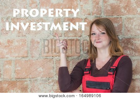 Attractive young redhead woman is standing in front of an old brick wall. Woman is looking at the camera and is pointing the finger at the sign Property Investment