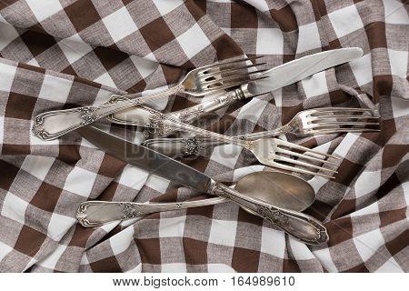 Silverware on a creasy white and brown checked cotton fabric closeup