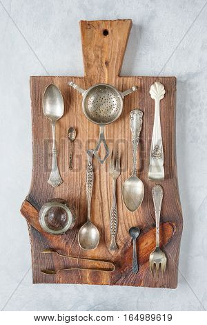 Various tableware on a wooden cutting board. Vertical image