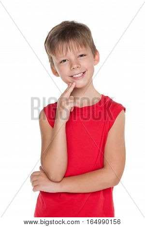 A smiling young boy in a red shirt on the white background
