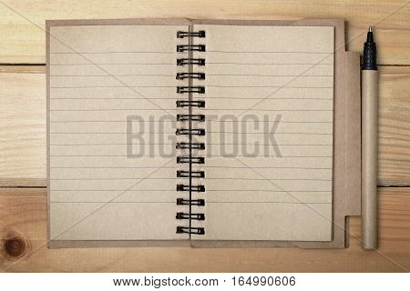 Open recycled paper note book with a pen over wooden background ecology concept ready to write text.
