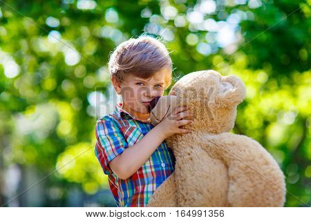 Little preschool kid boy playing with his big plush toy bear, outdoors. Child enjoying warm summer day in nature landscape
