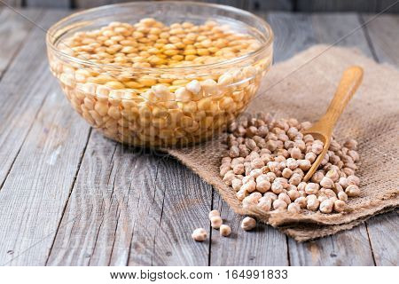 Chickpeas soaked in water in a bowl on wooden background