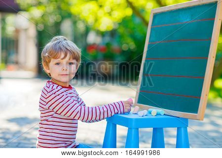 Adorable funny little kid boy at blackboard practicing writing letters, outdoor school or nursery. Child having fun with learning. Back to school concept.