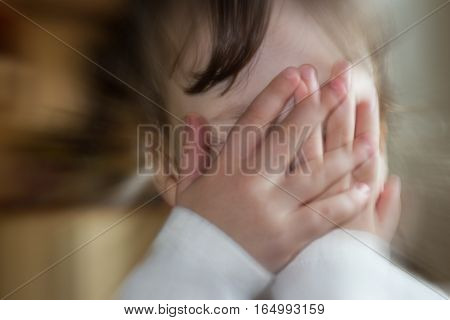 Blurred portrait of sad crying little girl covering his face with hands. Concept of child abuse. Shallow DOF. Defocused blurry background.