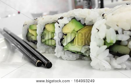 Japanese cuisine. Closeup of fresh veggie maki rolls with avocado.
